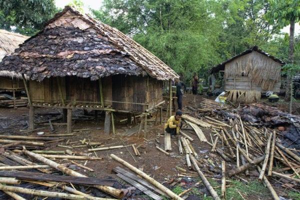 thailand hilltribe karen man kneeling next to a grass-roofed bamboo house