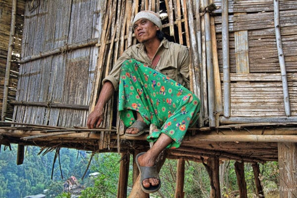 a lahu hilltribe man with green pants on is sitting next to bamboo house while looking out into the forest
