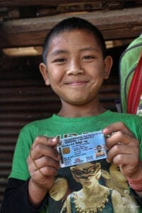 an indigenous lahu hilltribe boy proudly holding up his blue thai ID card