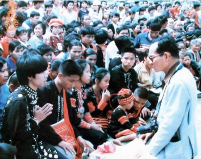 King <em>Bhumibol Adulyadej</em> (Rama IX) is sitting in front of many indigenous lahu hilltribe people