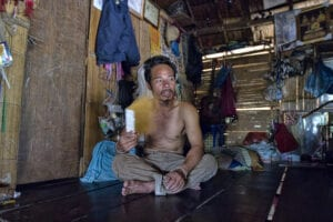 Tior, a Karen Thailand hilltribe man, is sitting on the floor.