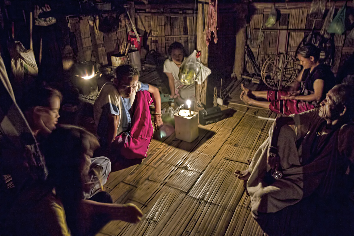 a family of thailand's hilltribe people are sitting on the floor a bamboo house and a candle is lit and placed in the middle of the room