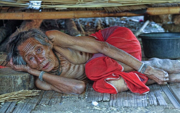 an old karen hilltribe man of nam bor noi village is lying on his side
