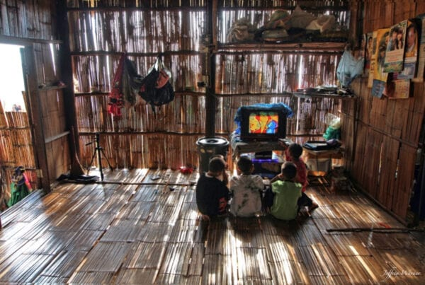lahu hilltribe youth are on the floor of a bamboo house while watching color television