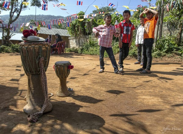 lahu hilltribe youth at the traditional new year celebration are wearing modern clothing and drinking coca cola while looking at the traditional drum youth at, and not participating in, their village's annual New Year festival.