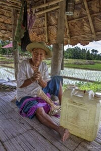 kabuwa, an indigenous karen hilltribe man, is sitting on the floor; he wearing traditional karen pants and a straw hat