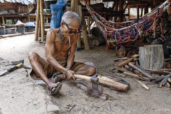 an old karen hilltribe man in nam bor noi village is cutting wood