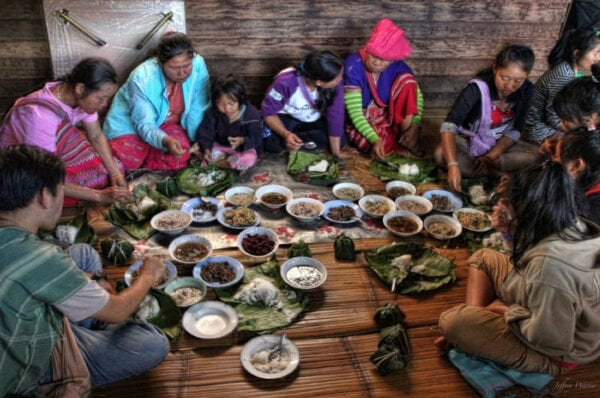 karen hilltrbe people are sitting on the floor eating together while surrounding many bowls of food