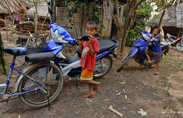 indigenous ethnic Karen hilltribe kids in nam bor noi village are looking into the mirror of a motorbike