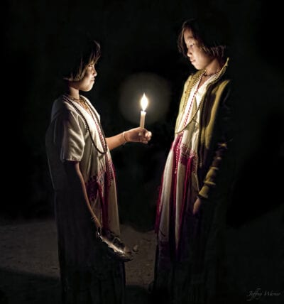 indigenous hilltribe karen hilltribe youth wearing white dresses are standing in complete darkness while looking at a candle