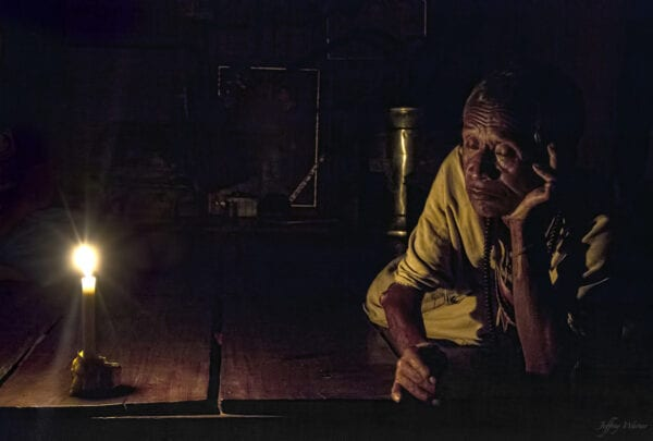 an old karen hilltribe man is lying on the floor with his eyes closed while a candle is lit