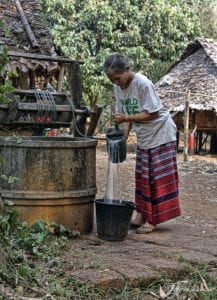 A karen hilltribe woman is pouring pouring well water into a black bucket.