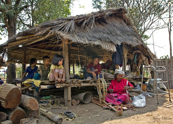 several generations of nam bor noi karen village are sitting in a bamboo hut and watching an elder weave