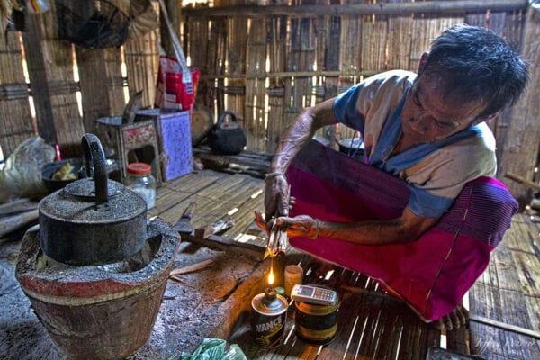 old karen man lighting a fire using an oil lamp